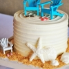 small-beach-inspired-cake-with-white-chocolate-shells-and-turquoise-adirondak-chair-topper