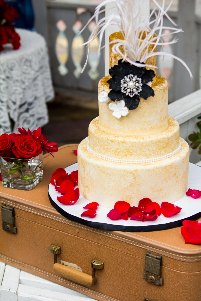 gold-speckled-cake-with-white-feathers-black-flower-vintage-glamour-683x1024