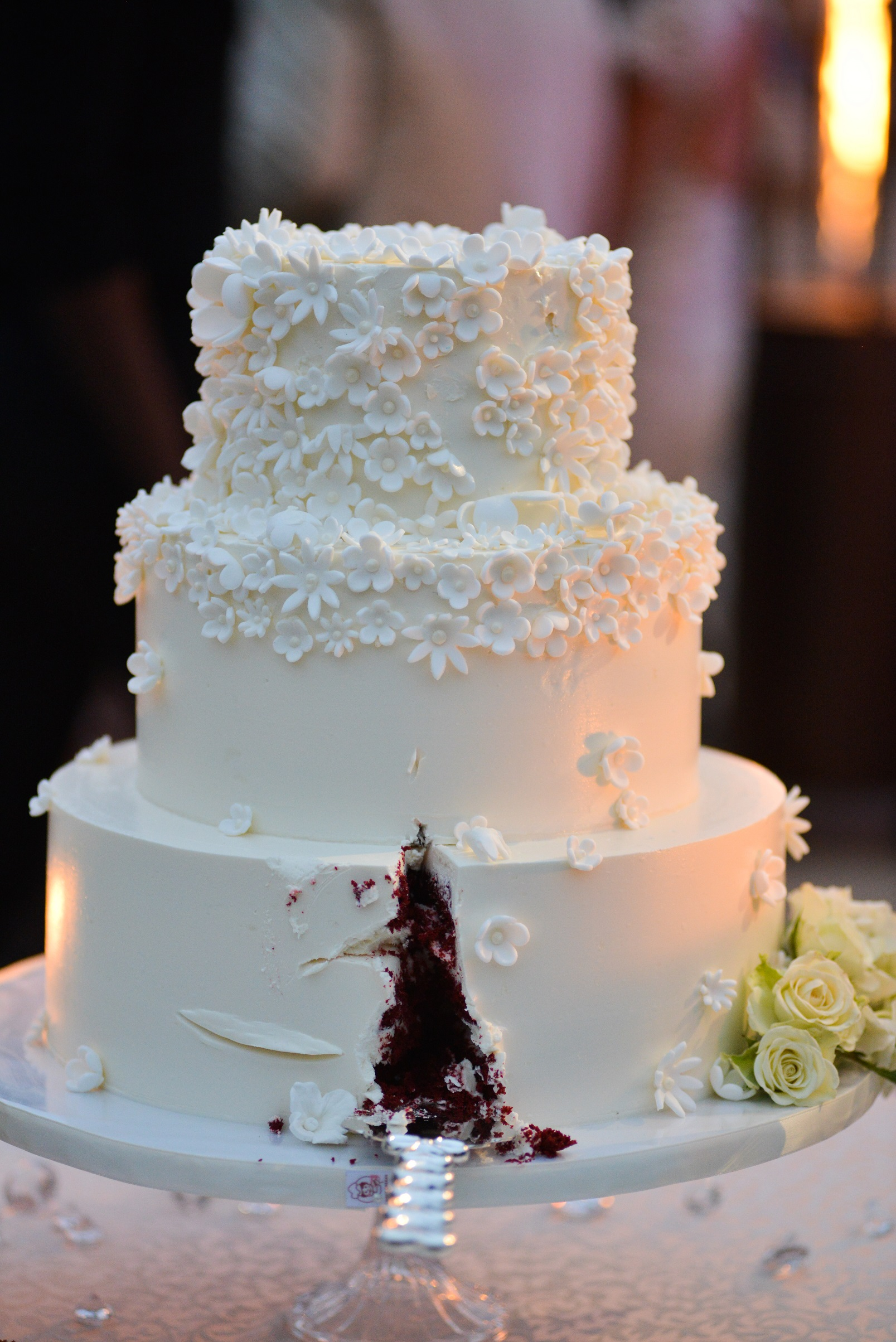 Cut chocolate wedding cake with white florets